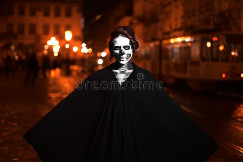 Mujer joven que presenta en la calle en traje negro con el maquillaje de Halloween Cintura para arriba Fondo de la ciudad de la n imagenes de archivo