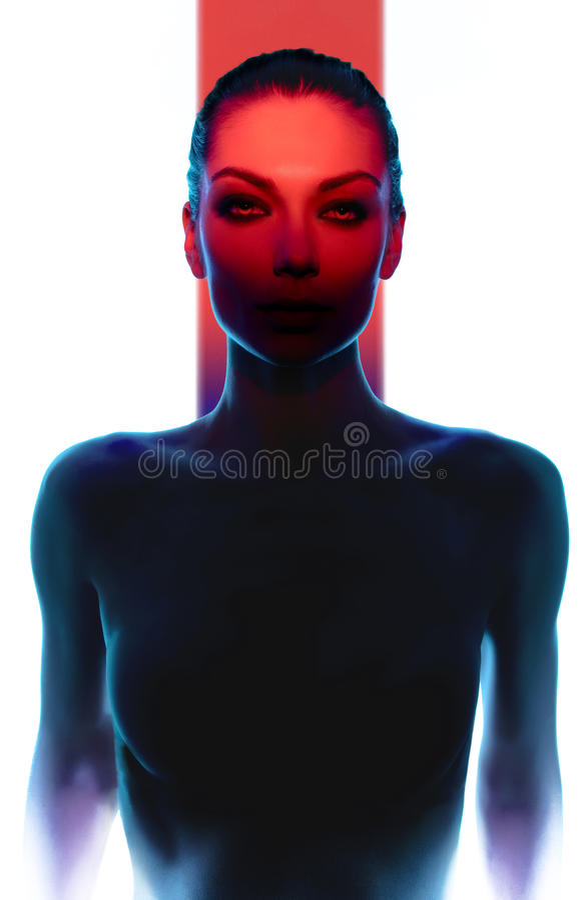 Mujer joven que presenta en oscuridad con la luz roja fotografía de archivo