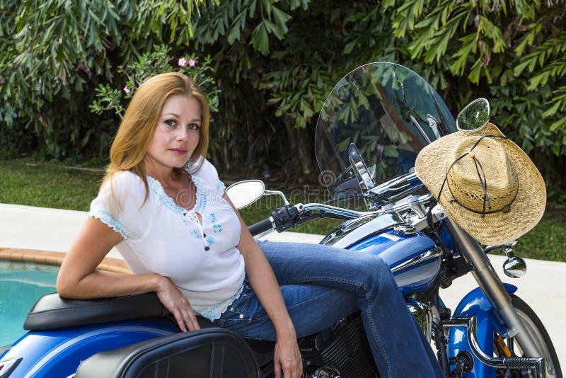 Mujer joven que presenta en una motocicleta imagenes de archivo