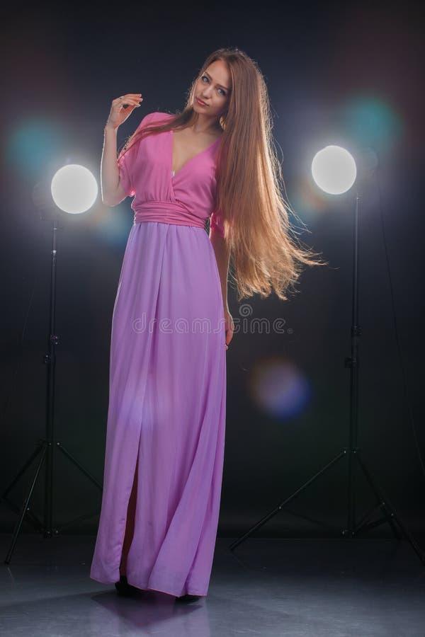 Mujer joven que presenta en vestido largo foto de archivo
