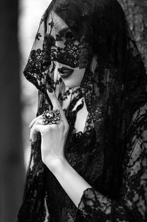 Mujer joven que presenta en vestido negro del cordón imagen de archivo