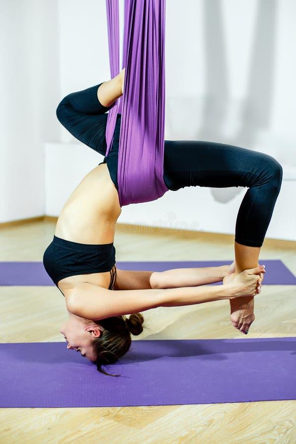 Mujer joven que presenta haciendo ejercicio aéreo de la yoga con la hamaca al revés imágenes de archivo libres de regalías
