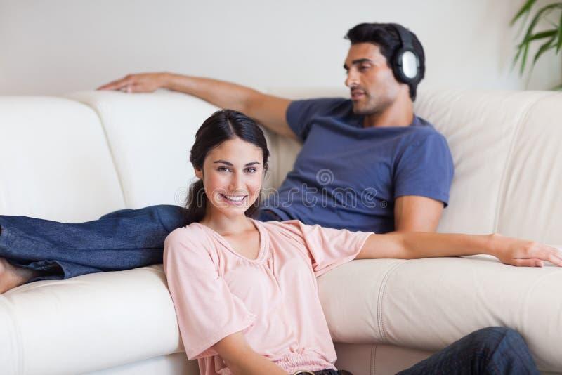 Mujer joven que presenta mientras que su marido está escuchando la música imagenes de archivo