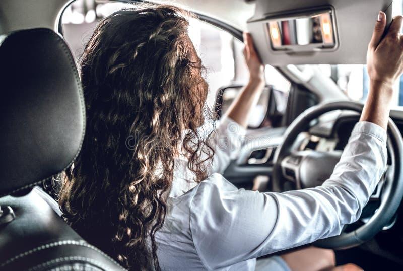 Mujer joven que prueba el nuevo coche en salón imágenes de archivo libres de regalías