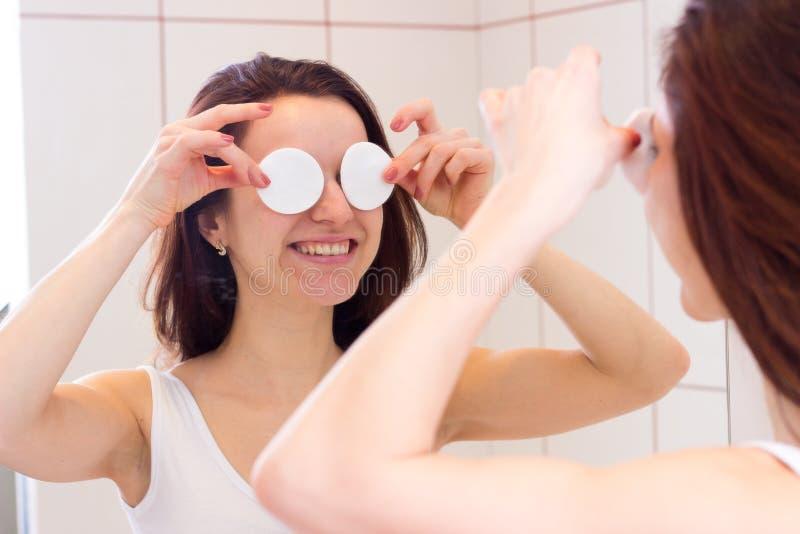 Mujer joven que quita maquillaje en cuarto de baño fotografía de archivo libre de regalías