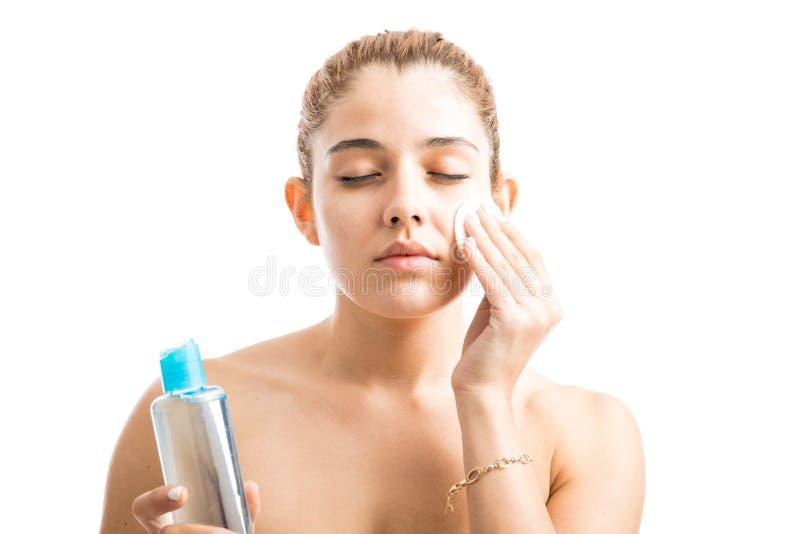 Mujer joven que quita su maquillaje imagen de archivo libre de regalías