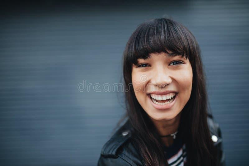 Mujer joven que ríe contra fondo gris imagenes de archivo