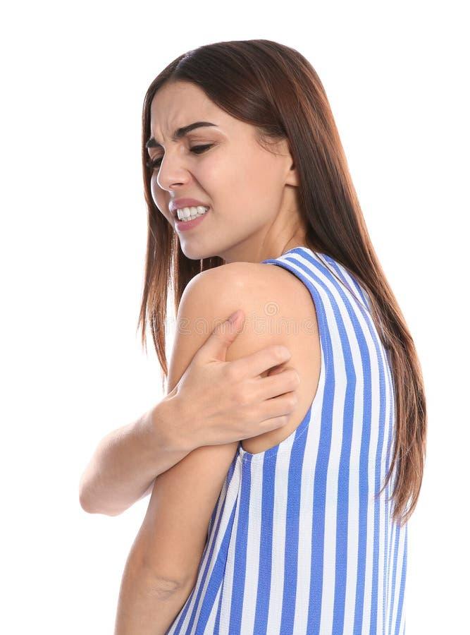 Mujer joven que rasguña el hombro en el fondo blanco fotos de archivo libres de regalías