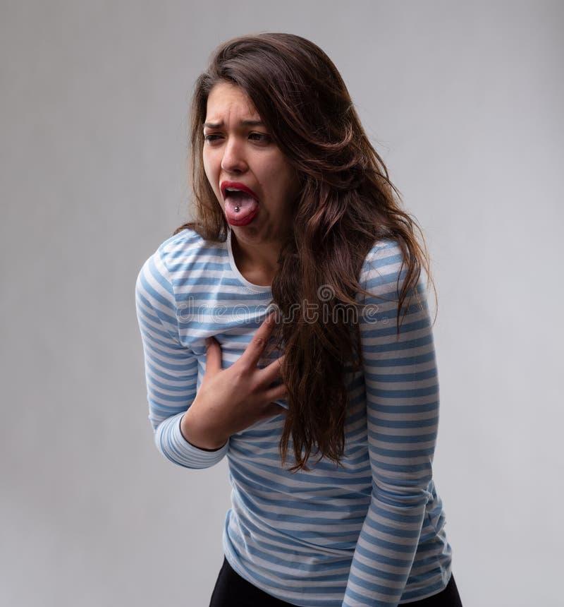 Mujer joven que reacciona con la repugnancia y el repugnancia foto de archivo