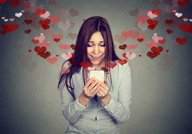 Mujer joven que recibe el mensaje de texto del SMS del amor en el teléfono móvil foto de archivo libre de regalías