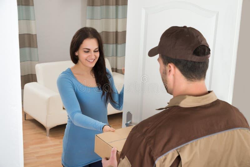 Mujer joven que recibe el mensajero de hombre de entrega fotografía de archivo