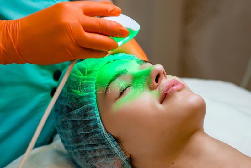 Mujer joven que recibe el tratamiento del laser de Epilation en cara en el centro de la belleza foto de archivo