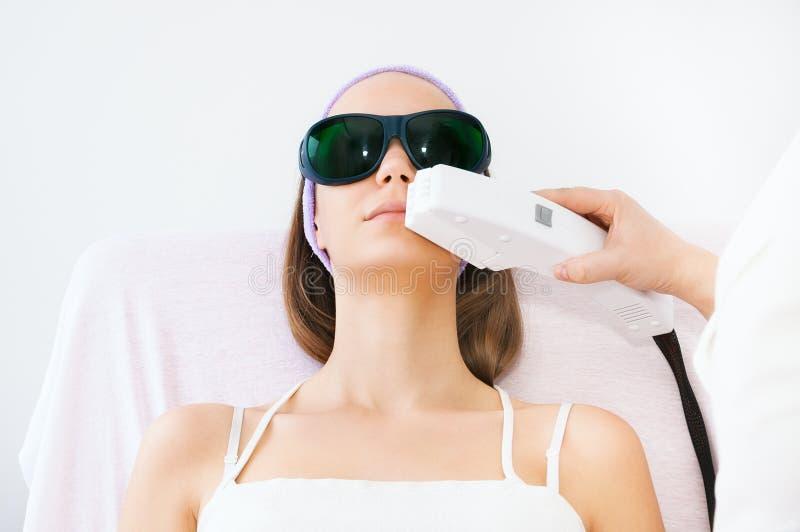 Mujer joven que recibe el tratamiento del laser del epilation imagen de archivo libre de regalías