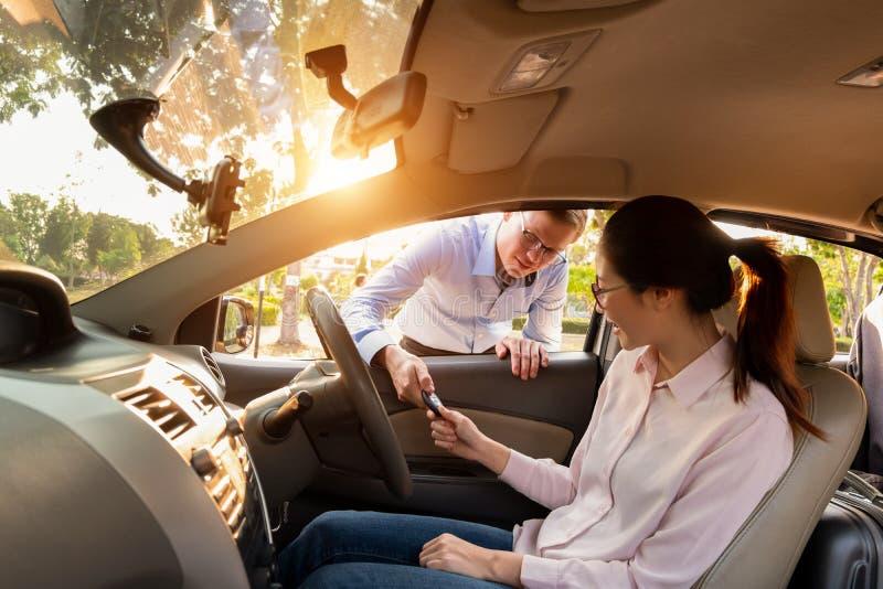 Mujer joven que recibe las llaves de distribuidor autorizado, concepto del coche de la venta imagen de archivo