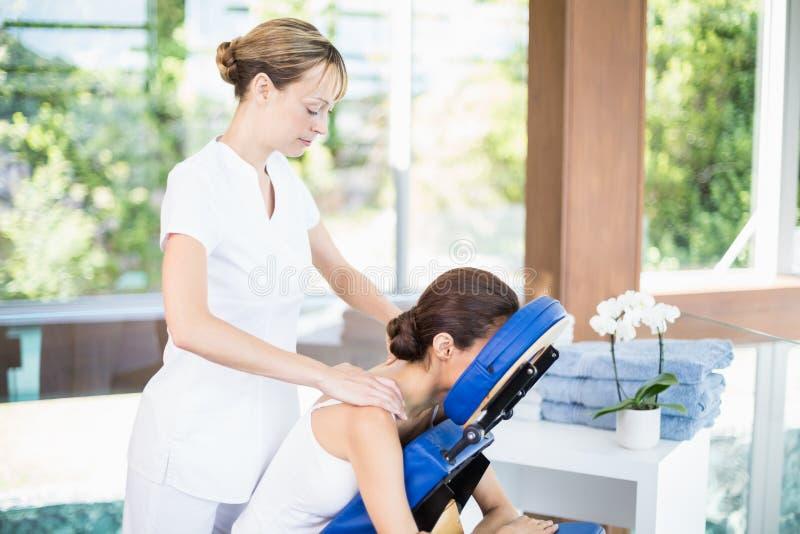 Mujer joven que recibe masaje del hombro imagen de archivo