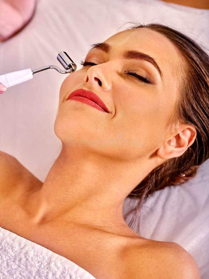 Mujer joven que recibe masaje facial eléctrico imagen de archivo libre de regalías