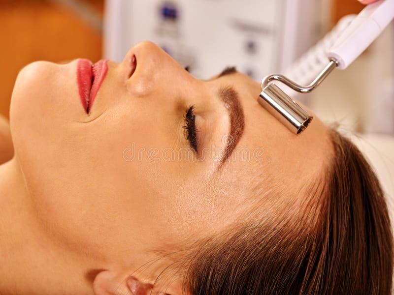 Mujer joven que recibe masaje facial eléctrico fotos de archivo