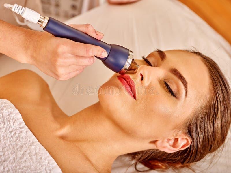 Mujer joven que recibe masaje facial eléctrico foto de archivo