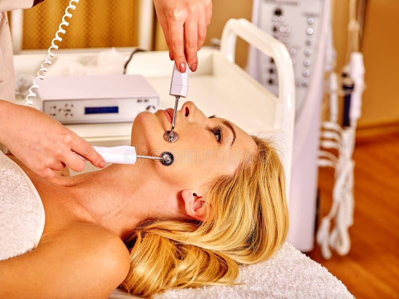 Mujer joven que recibe masaje facial eléctrico imagenes de archivo