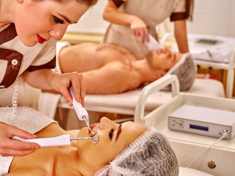 Mujer joven que recibe masaje facial eléctrico imagen de archivo