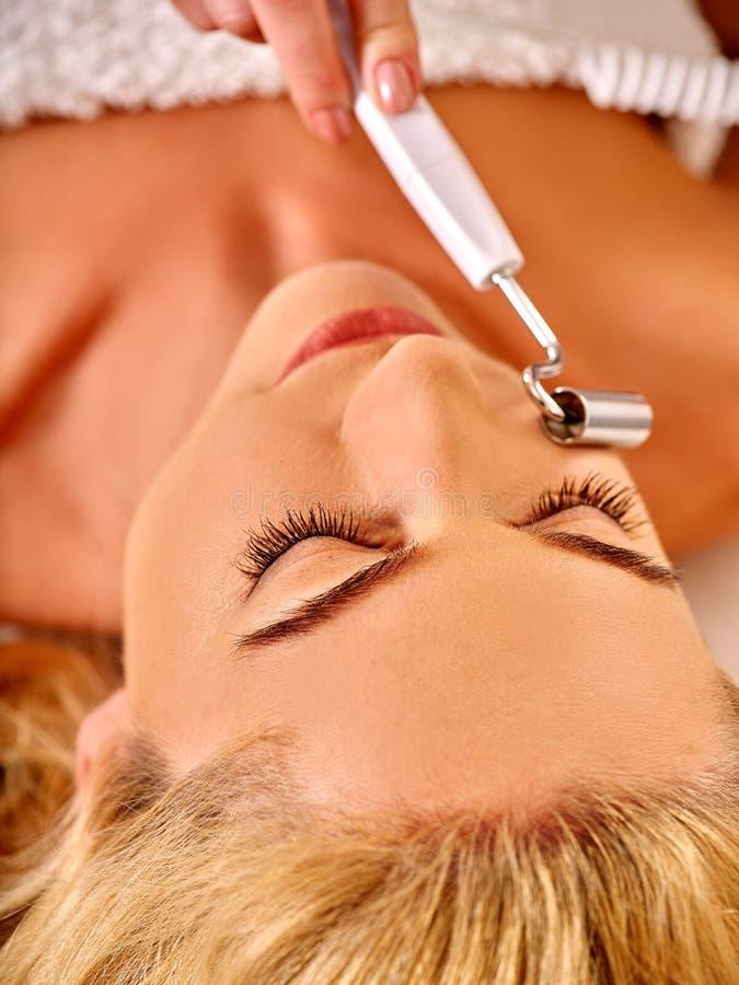 Mujer joven que recibe masaje facial eléctrico foto de archivo libre de regalías