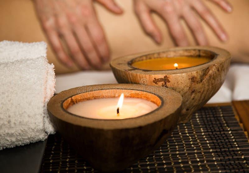 Mujer joven que recibe un masaje trasero en el salón del balneario primer de una vela y de toallas imagen de archivo