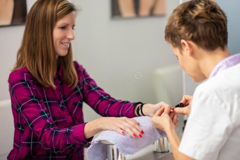 Mujer joven que recibe un tratamiento de la manicura fotografía de archivo