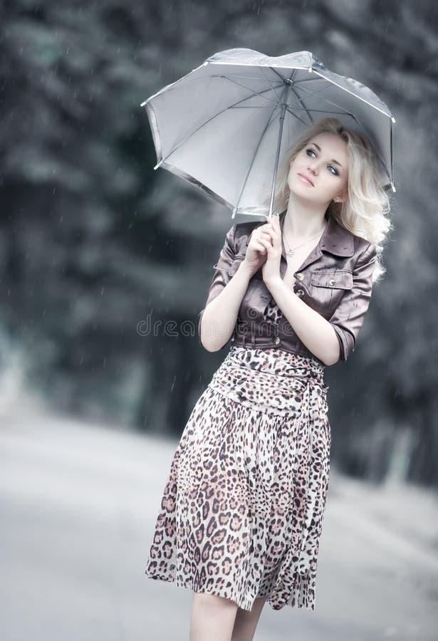 Mujer joven que recorre con el paraguas foto de archivo
