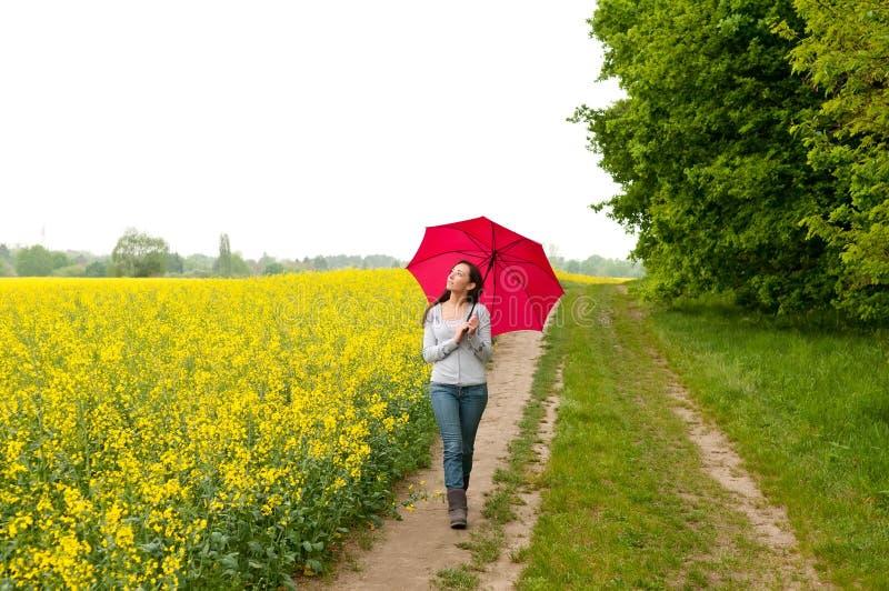 Mujer joven que recorre con el paraguas fotos de archivo
