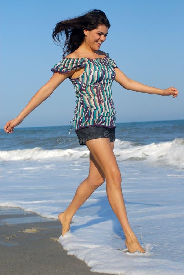 Mujer joven que recorre en la playa foto de archivo libre de regalías