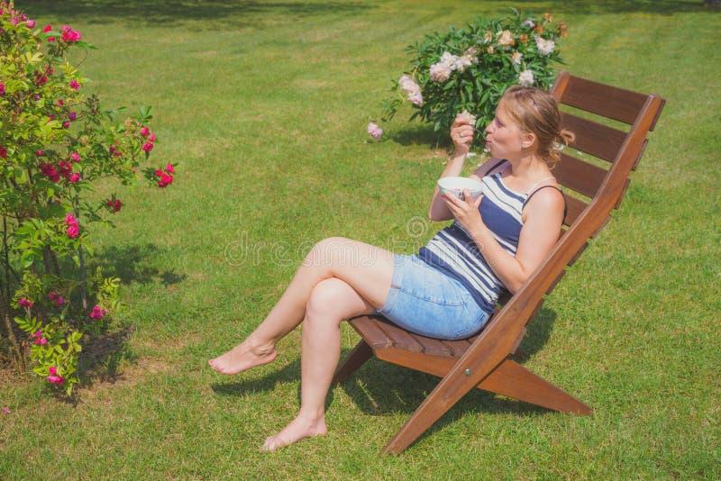 Mujer joven que relaja y que come el helado imagenes de archivo