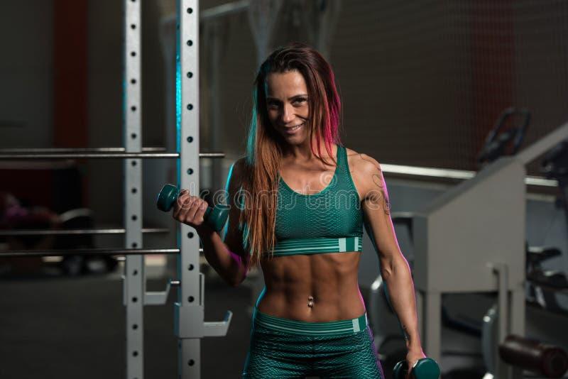 Mujer joven que resuelve el bíceps con pesas de gimnasia imagen de archivo libre de regalías