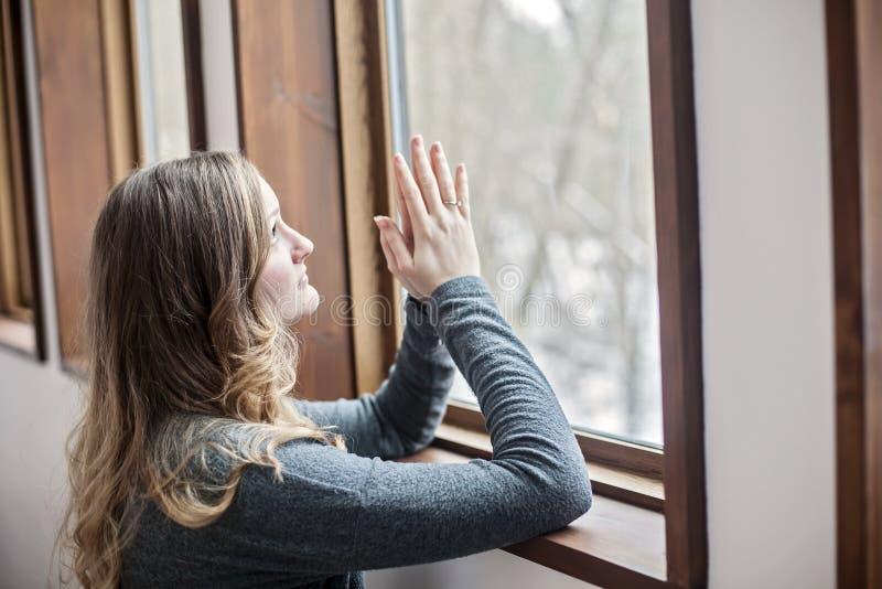 Mujer joven que ruega por la ventana foto de archivo