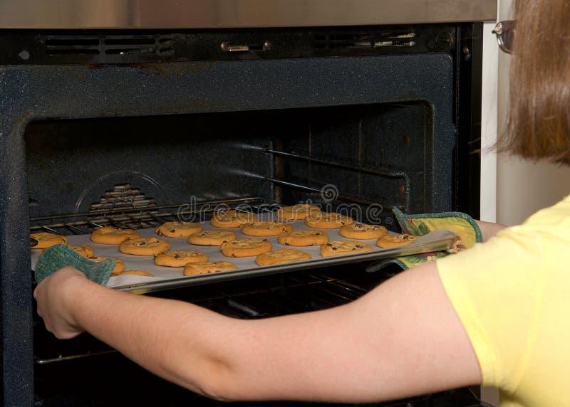 Mujer joven que saca de las galletas de microprocesador de chocolate el horno fotos de archivo libres de regalías