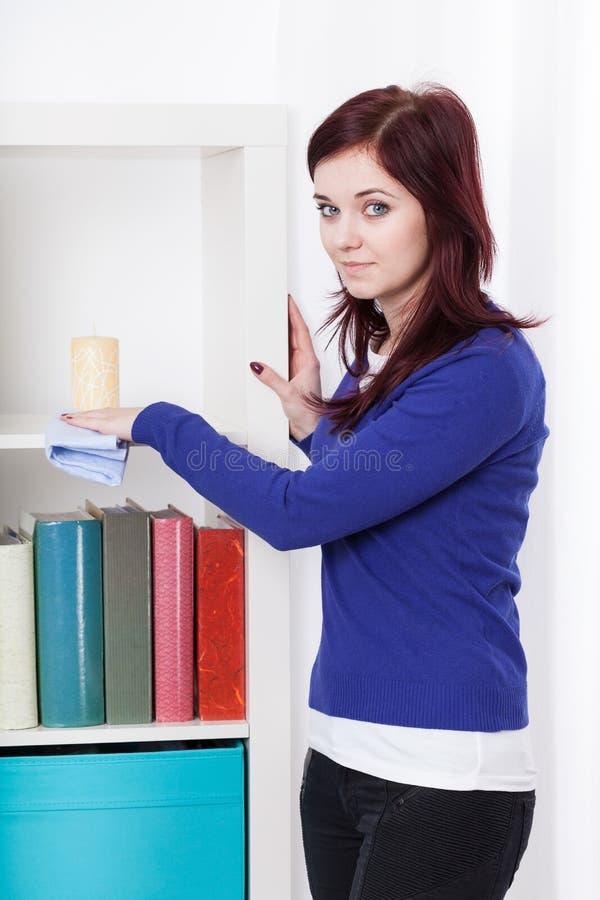 Mujer joven que saca el polvo de un estante para libros imagenes de archivo