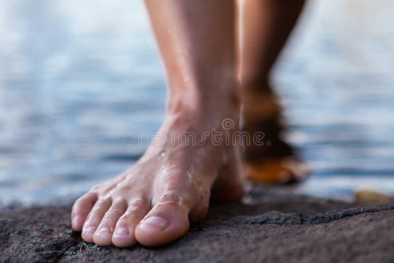 Mujer joven que sale de los pies desnudos del agua en una roca fotografía de archivo