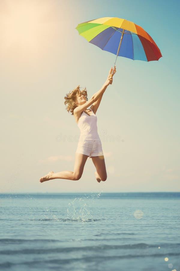 Mujer joven que salta con el paraguas del arco iris en la playa Escena de fotos de archivo