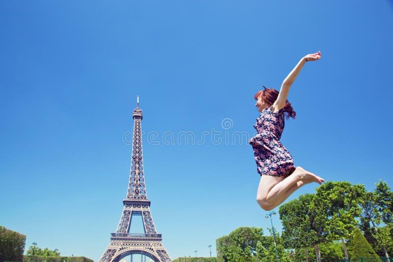 Mujer joven que salta contra torre Eiffel imagenes de archivo