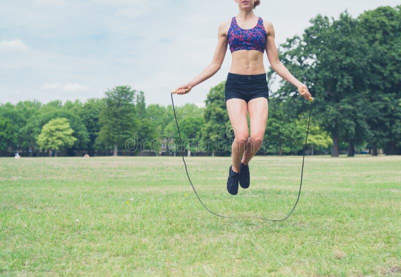 Mujer joven que salta en el parque fotografía de archivo