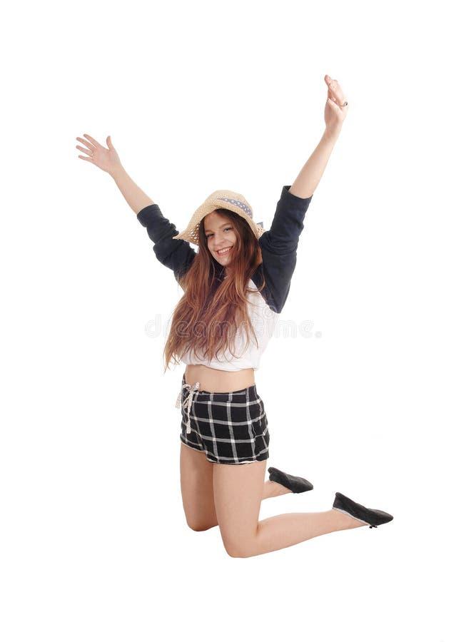 Mujer joven que salta en pantalones cortos y sombrero imagen de archivo