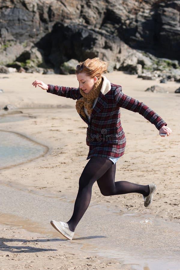 Mujer joven que salta a través de corriente en la playa imagenes de archivo