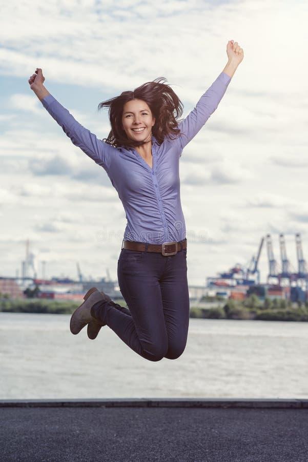 Mujer joven que salta y que anima para la alegría imagen de archivo libre de regalías