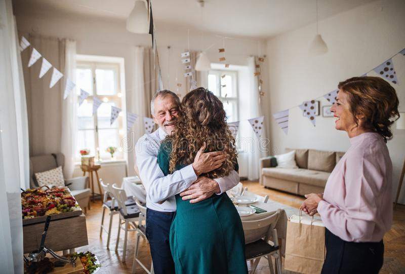 Mujer joven que saluda padres o a abuelos en una fiesta de cumpleaños interior foto de archivo