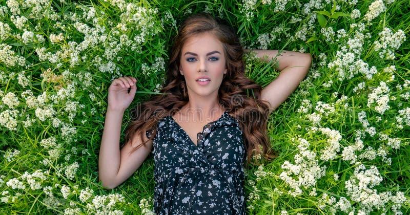 Mujer joven que se acuesta en las flores blancas de la lavanda imágenes de archivo libres de regalías
