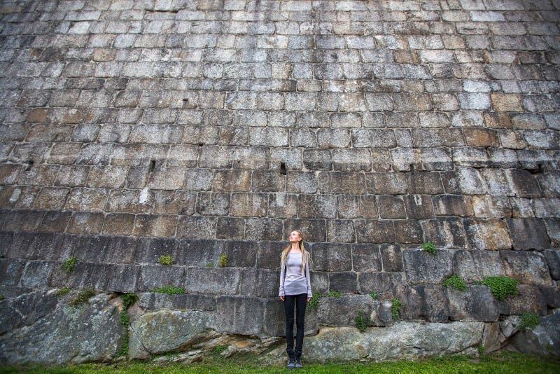 Mujer joven que se coloca cerca de una pared de piedra enorme Configuración fotos de archivo libres de regalías