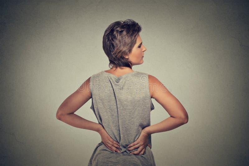 Mujer joven que se coloca con dolor de espalda del dolor de espalda fotografía de archivo libre de regalías