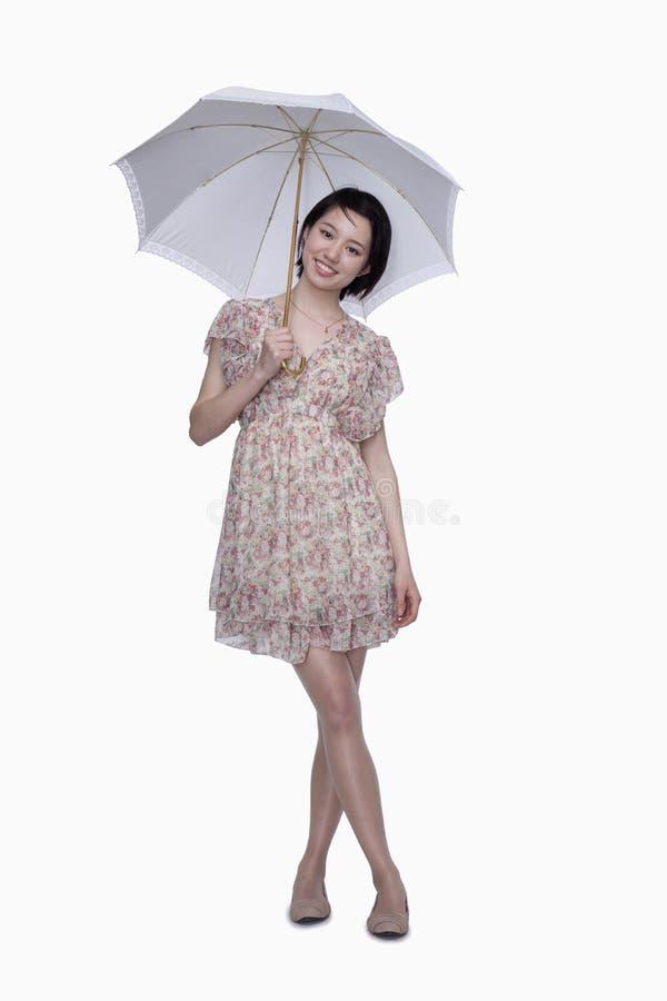 Mujer joven que se coloca con el paraguas fotografía de archivo