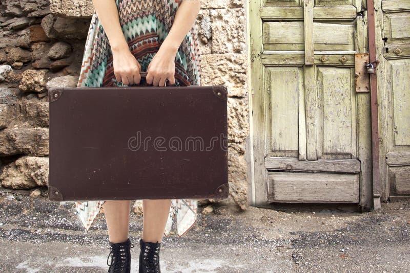 Mujer joven que se coloca con la maleta en el camino fotografía de archivo libre de regalías