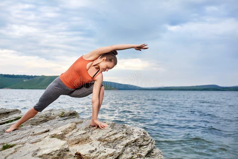Mujer joven que se coloca en actitud de la yoga en el río hermoso cercano de piedra grande fotos de archivo
