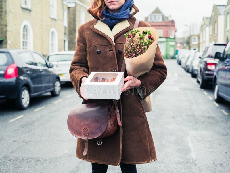 Mujer joven que se coloca en calle con la torta y las flores imágenes de archivo libres de regalías